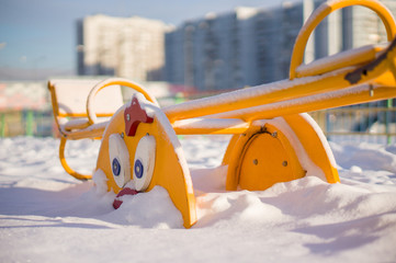 Kids metal swing on winter playground covered with snow