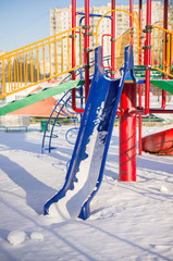Kids huge slide on winter playground covered with snow