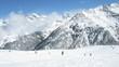Skiers climb down mountain Tiefenbachkogl on skis against