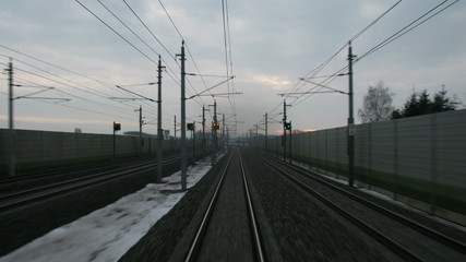Train goes by rail near with inhabited locality along electric