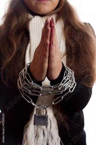 woman's hands tied with a chain on a white background