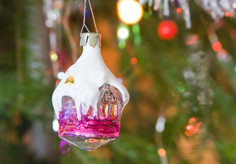 new-year toy a house hangs on a christmas tree