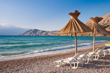 Sunshade and deck chair on beach at Baska in Krk - Croatia