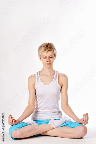 Young woman practising yoga in lotus position