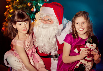Santa Claus holding  bag and little girl holding gift