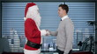 Santa Claus and Young Businessman in office, shaking hands