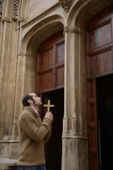 Man praying in church holding prayer beads