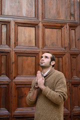 Man praying in front of the church holding prayer beads