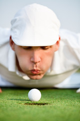 Close-up of man blowing on golf ball
