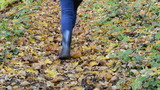 woman climb hill on autumn colorful leafy forest path