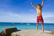 young happy child boy jumping on tropical sea background