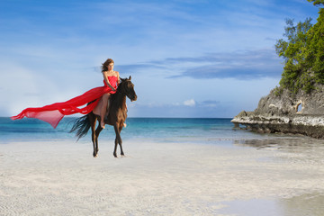young beautiful woman riding a horse on tropical beach