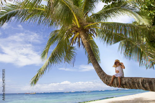 young happy child girl in summer hat on tropical sea background