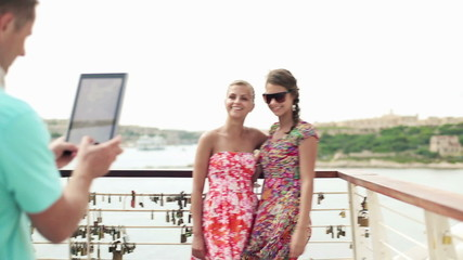 Friends taking photo with tablet computer on vacations