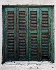 Wooden turquoise window on a white house in Sarti, Greece