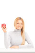 A smiling blond female holding a red apple on a table