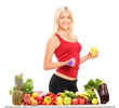 Female athlete holding a dumbbell and glass of juice behind a ta