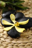 yellow orchid and black stones on woven mat