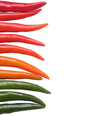 Colorful chillies border isolated on white background. These chi