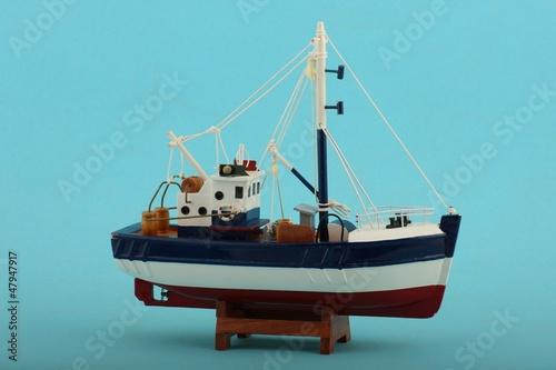 canvas print picture Fischerboot model mit blauem Hintergrund