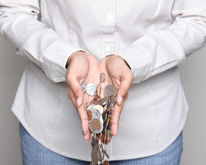 Woman holding coins in her hands - wealth