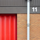 Unit 11 with red shutter, guttering and bricks poster
