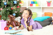 Little girl writing letter to Santa near christmas tree