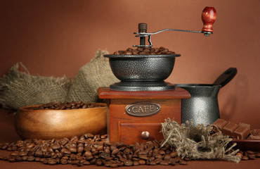 Coffee grinder, turk and coffee beans on brown background