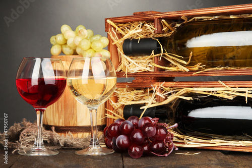Wooden case with wine bottles, barrel, wineglasses and grape
