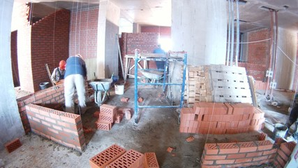 Workers build walls from brick