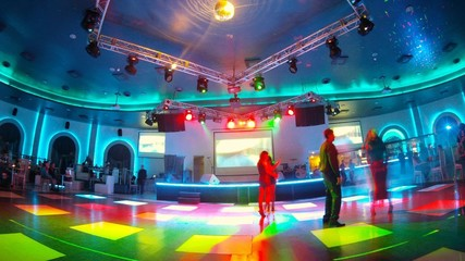 Group of people dance in night club on dancefloor