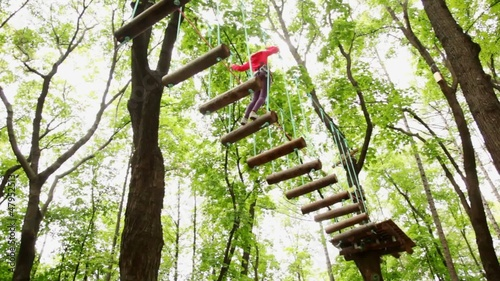 girl fixed on insurance, jumps on suspended by ropes on trees to