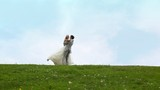 Newly-married couple runs to each other, embraces, then bride