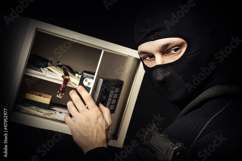 Professional burglar in black ski mask