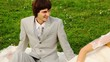 Newly-married couple sits on meadow and bride blows in party