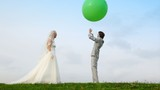 Newly-married couple throws upwards together inflatable sphere