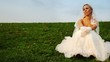 bride in white dress sits one on grass on hill slope