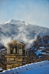 A mountain house roof with smoking chimney