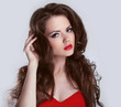 Woman with beauty long brown hair and red lips, red dress- posin
