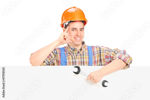 Male construction worker standing behind a panel