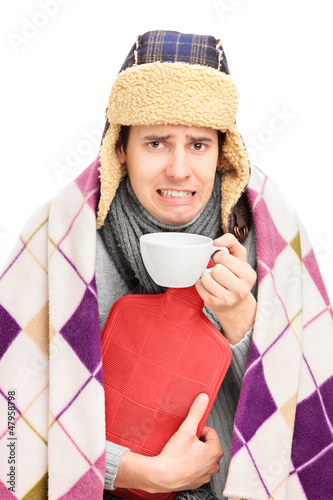 Sick guy covered with blanket holding a hot-water bottle and dri