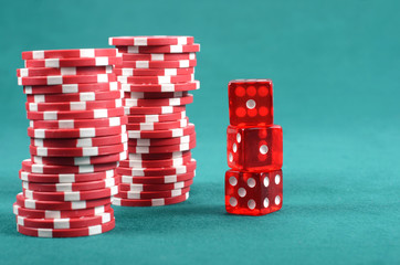 Red poker gambling chips on a green playing table