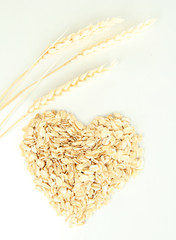 Heart shape made from oat flakes with spikelets isolated