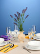 Table setting in violet and yellow tones on color  background