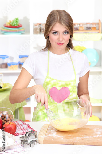 A young girl in kitchen during cooking biscuits