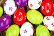 bemalte bunte Eier für Ostern versteckt im Nest aus Stroh