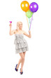 Full length portrait of a pretty blond female holding balloons a
