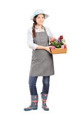 Full length portrait of a female gardener holding flower plants