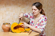 young woman  cuts pumpkin