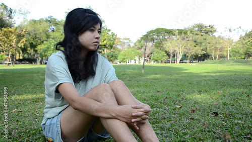 Young, sad, lonely beautiful woman in the park